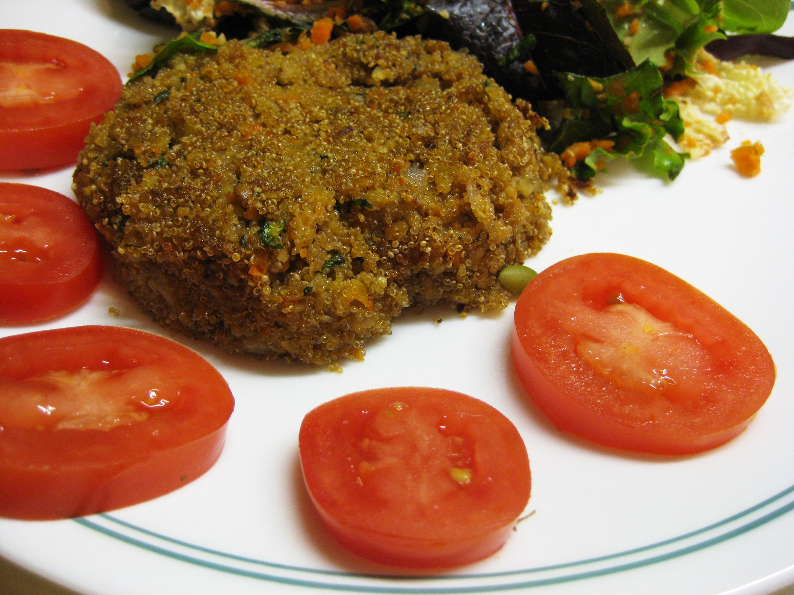 Herbed Amaranth Cakes on a plate with tomatoes and salad